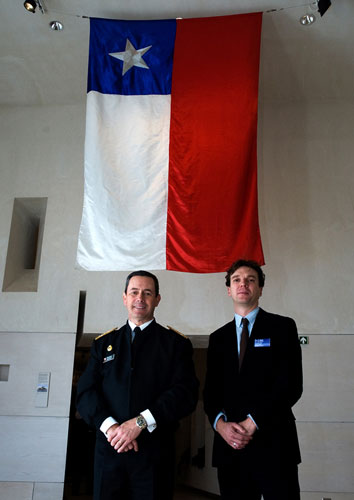 Admiral Edmundo Gonzalez, Commander-in-Chief of the Navy of Chile and lead curator Stuart Allan with the ensign from the Almirante Cochrane.