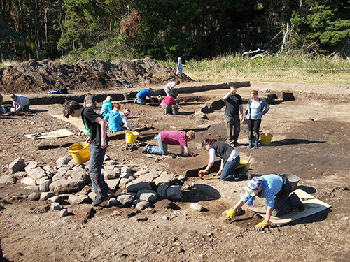 cleaning off the last of the ploughsoil to show the archaeological traces