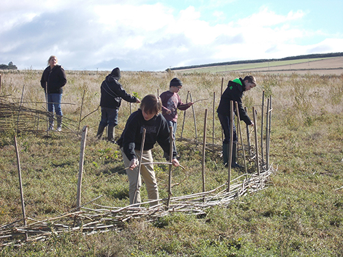 Lhanbryde kids learning how to build a roundhouse.