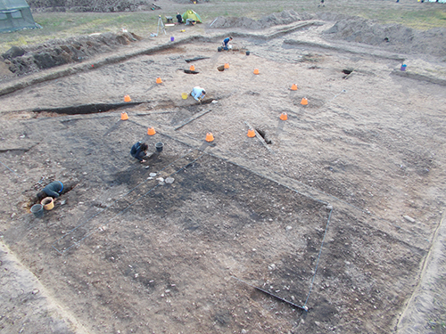 Our big roundhouse, with the natty orange buckets marking where posts once stood. You can see where we've dug through the hollow where the cattle were once kept.
